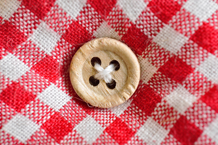 nger: wood Button on checkered textile Stock Photo