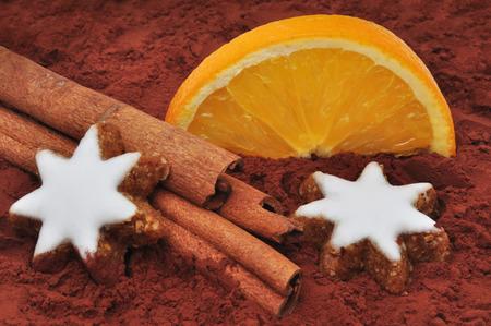 Zimtstange und Orange auf Kakaopulver