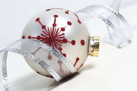 weihnachtsbaum: silver ribbon and christmas bauble on white background Stock Photo
