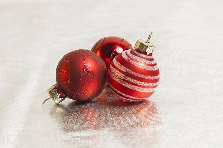 rote Weihnachtskugeln auf Silber Textil Standard-Bild