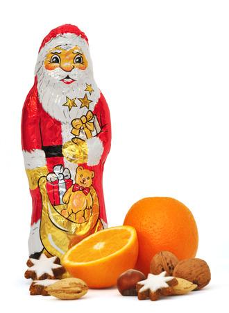 chocolate santa clause with orange, cinnamon stars and nuts photo