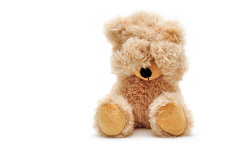 brown teddy holds his paws over his eyes