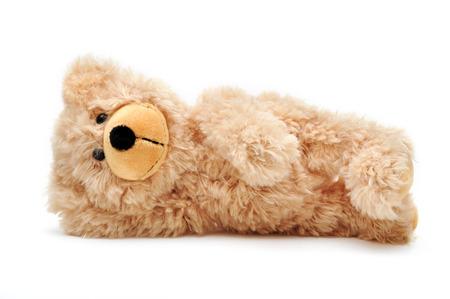 spiel: brown teddy bear lying on its side