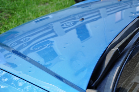 hail damage on the hood of a blue car Stock Photo
