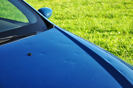 damages: hail damage on the hood of a blue car Stock Photo