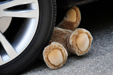 sch: Teddy under car tires, symbolic car accident with playing children
