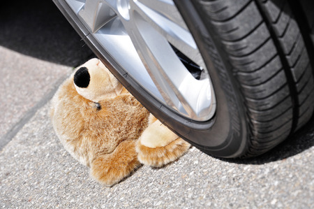 toy car: Teddy under car tires, symbolic car accident with playing children