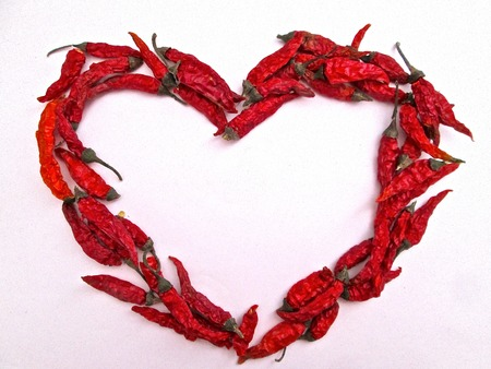 Heart shape made from chilli peppers on a white paper background photo
