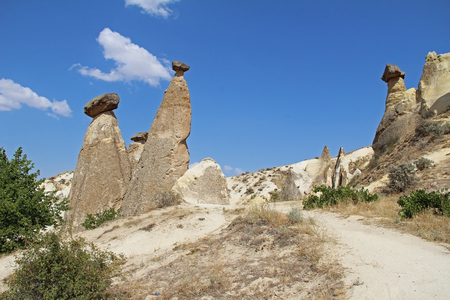 Natural valley with volcanic tuff stone rocks dramatically lit by a sun in Chavushin in Cappadocia, Central Anatolia region of Turkey. Popular tourist destination in Turkey for trekking. Stock Photo