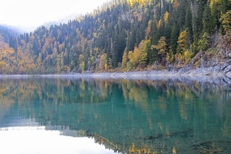 Beautiful lake surrounded by mountains and forests in autumn, Malaya Ritsa, Abkhazia. 스톡 콘텐츠 - 114974488