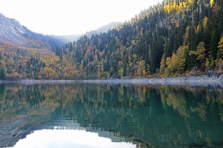 Beautiful lake surrounded by mountains and forests in autumn, Malaya Ritsa, Abkhazia. 写真素材 - 114974489