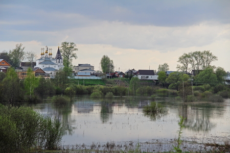 Spill the river in the fields near the village in early spring in cloudy weather. Russia. 写真素材