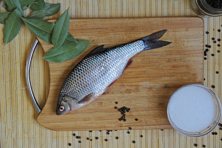 Fresh river fish roach with spices salt, pepper, bay leaf on a cutting wooden board. Russia.