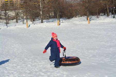 In winter, the girl goes up the mountain in the snow and carries a tubing.