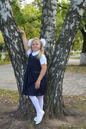 A smart girl in a school uniform with white bows on the first of September