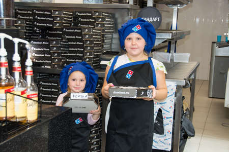 Children at a master class on pizza preparation in the pizzeria Dominos pizza.