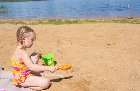A girl plays on a sandy beach on the shore of the lake in the summer heat.