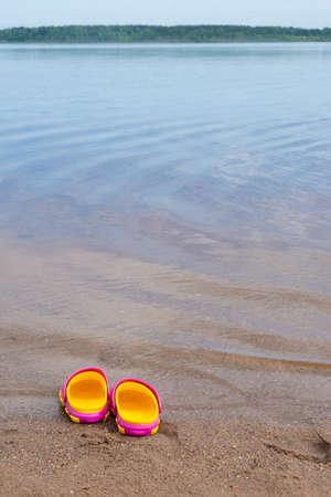 Children's pink clogs stand on a sandy beach near the water.