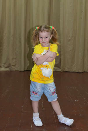 The girl dances on the stage in a beautiful bright costume interesting dance.