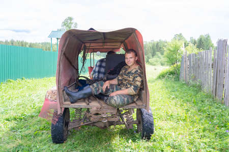 A teenager sits in the trailer of a makeshift all-terrain vehicle with a trailer.