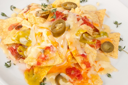 closeup of nachos with cheese and olives