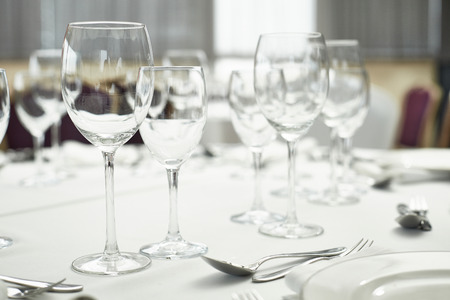 restaurant table setout with white plates and silverware and wine glass photo