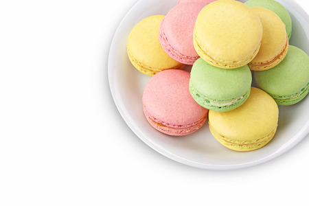 fresh red, green and yellow macaroons on white plate