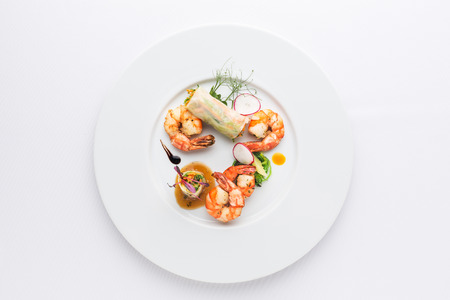 prepared shrimps, spring rolls and salad on white plate