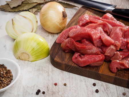 raw meat slices on cutting board with pepper and onion