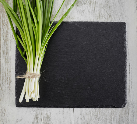 spring onions on dark board
