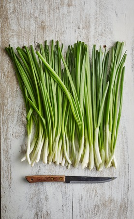 spring onions on rustic light gray wood