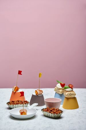 Finger food with party flags on pink backdrop