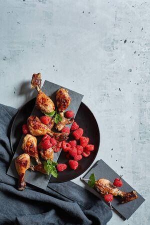 Chicken wings with raspberries on cement background