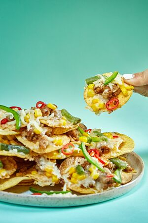 Nachos with fingers on blue background