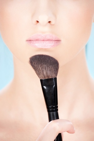 Part of a womans face and makeup brush photo