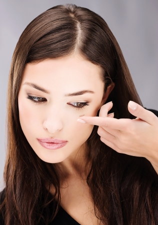 eyes contact: Young brunette woman holding contact lens on finger in front of her eye Stock Photo