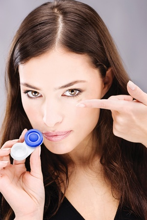 wearer: Young woman holding contact lenses cases and lens in front of her face