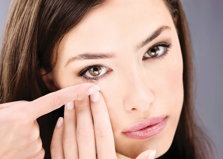 lentes de contacto: Primer plano de una mujer poniendo la lente de contacto en el ojo