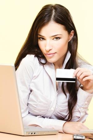 orden de compra: Joven y bella mujer sentada cerca de la computadora port�til y m�vil de la tarjeta de cr�dito celebraci�n de tel�fono en la mano izquierda