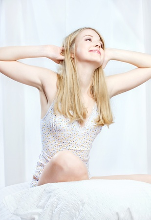 Young blond woman sitting on bed, stretching arms above head