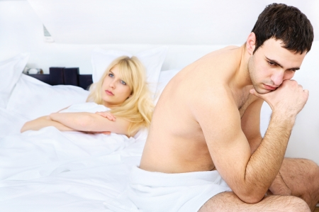 relationship difficulties of a young couple in bedroom, focus on male Stock Photo