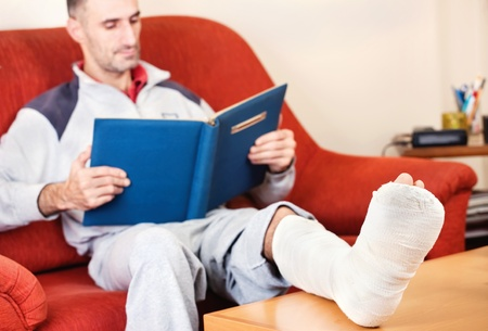 broken home: man with a broken leg on a sofa at home  reading book; focus on cast