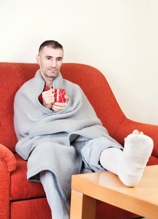 man with a broken leg on a sofa at home  holding cup of coffee photo