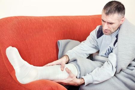 pierna rota: hombre con una pierna rota en un sofá en casa con el dolor