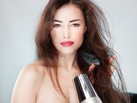 blow dryer: woman with long hair holding blow dryer