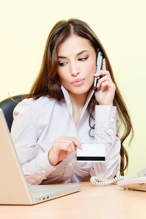 Pretty woman talking over phone, holding credit card and looking at the laptop photo
