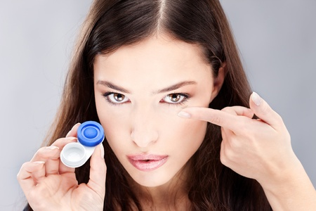 Young woman holding contact lenses cases and lens in front of her face photo