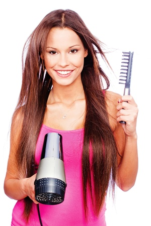 woman with long hair holding blow dryer and comb, isolated on white Stock Photo - 12369577
