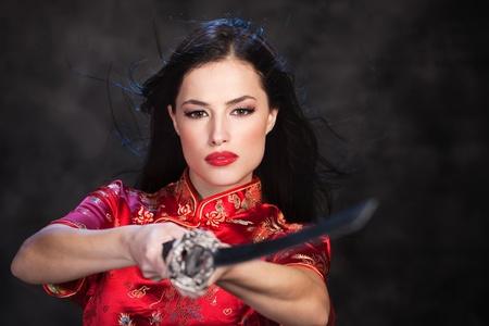 catfight: Pretty kimono woman in action with katanasword