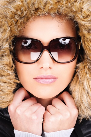pretty woman wearing winter outfit with fur and glasses  Stock Photo